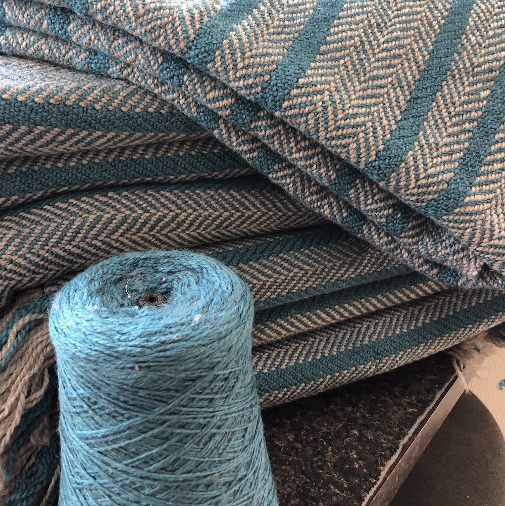 Handwoven blanket with cone of yarn
